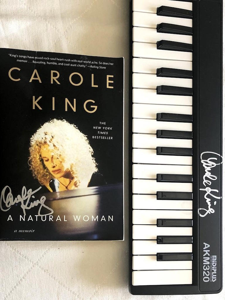 "Carole King signed a mini-keyboard and a copy of her autobiography ""A Natural Woman: A Memoir."""
